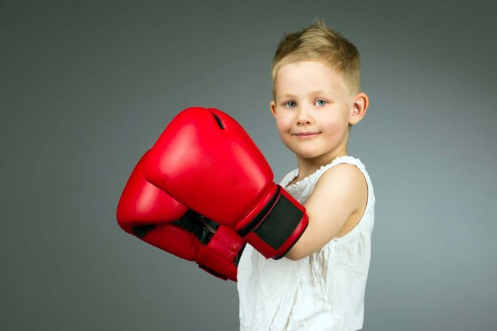 Мальчик в белой майке и красных боксёрских перчатках стоит боком и улыбается