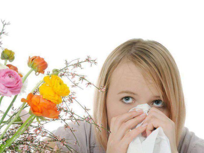 Девушка находится рядом с букетом цветов и закрывает нос платком