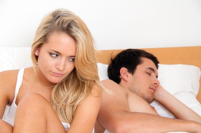 Женщина сидит в постели с мужчиной с недовольным видом