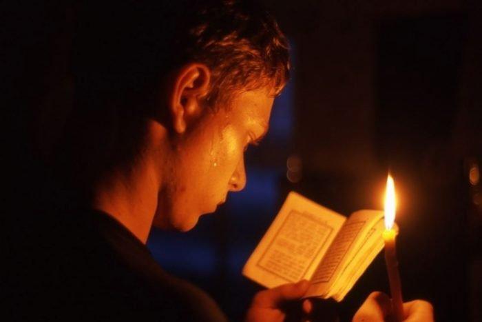 молодой человек читает молитву и держит свечу