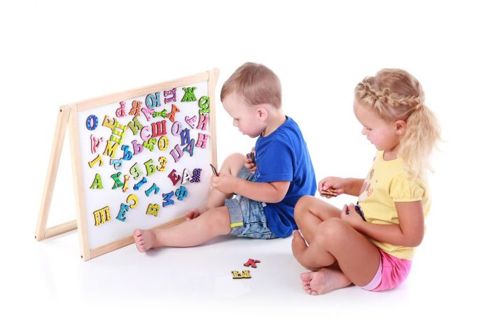 Мальчик и девочка рассматривают магнитную доску и буквы