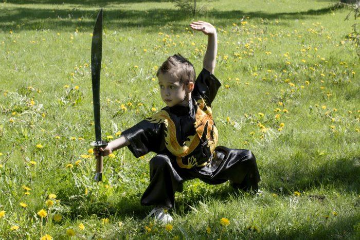 Мальчик стоит на траве в позиции из ушу с мечом в руке