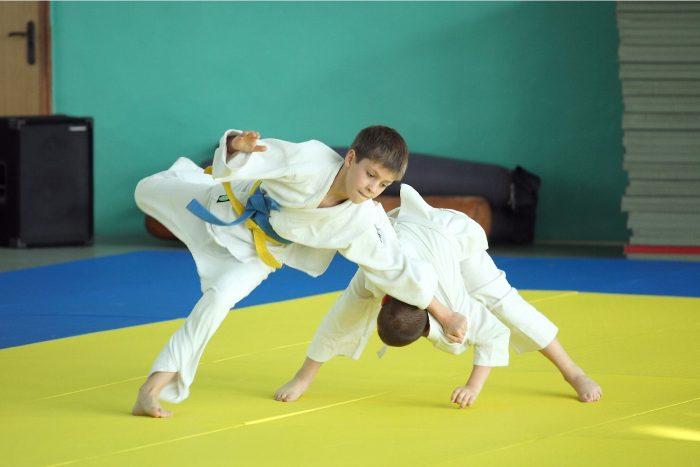 Два мальчика на татами в белых кимоно соревнуются в технике дзюдо