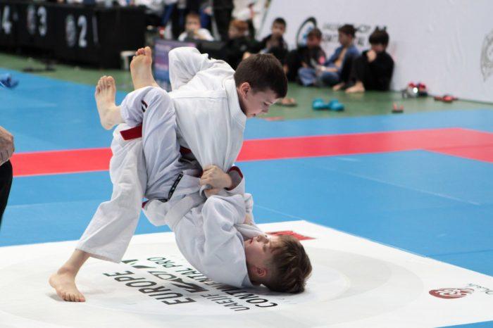 Два мальчика в белых кимоно на татами соревнуются в борьбе джиу-джитсу