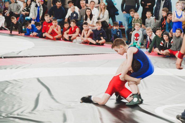 Соревнование по вольной борьбе между мальчиками. обхватившими друг друга за корпус на татами