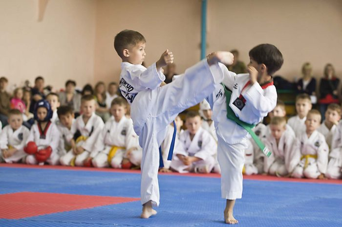 Два мальчика в белых кимоно участвуют в спарринге по технике тхэквондо