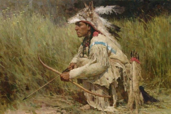 Индеец держит в руках лук с натянутой стрелой