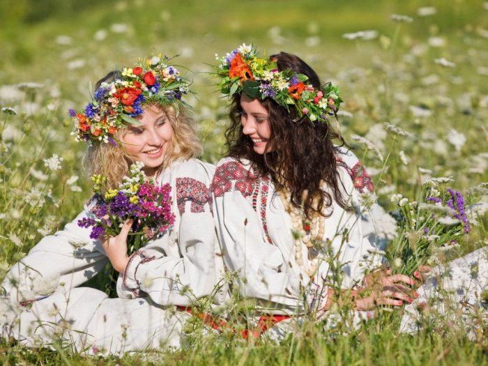 Девушки в крестьянской одежде и венках на голове силят в траве и смеются