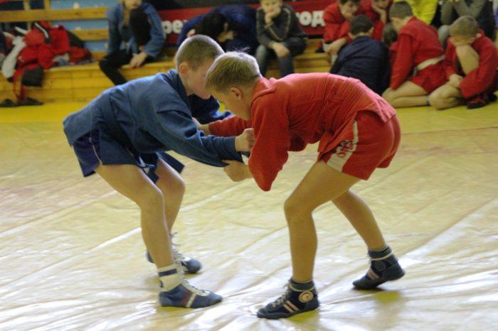 Два мальчика в синем и красном халате держат друг друга «за грудки» на соревновании по самбо