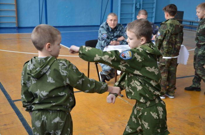 Два мальчика в армейской униформе демонстрируют тренеру свои умения в русском рукопашном бою