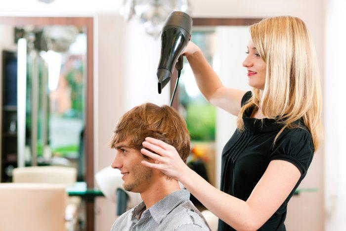 Парикмахер укладывает волосы мужчине