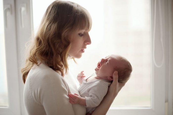 Мама держит плачущего новорождённого