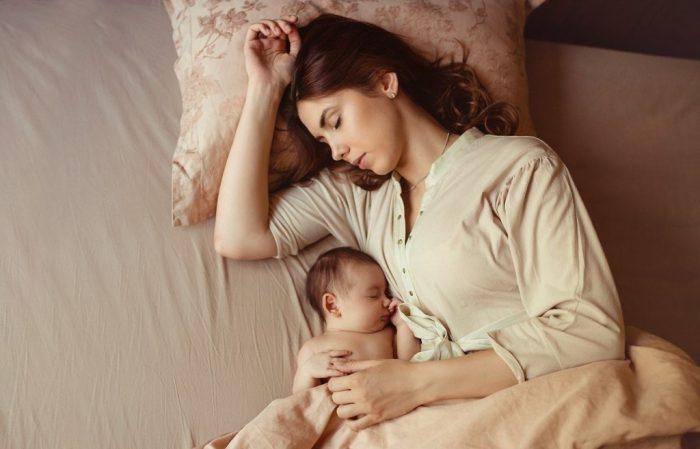 Мама спит с младенцем на кровати