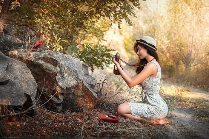 Девушка фотографирует птицу