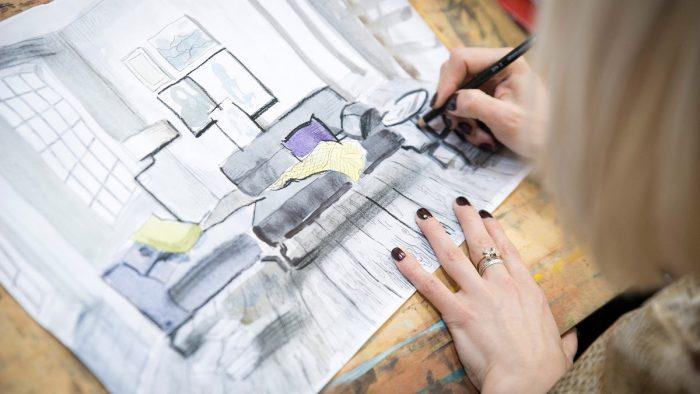 Девушка рисует дизайнерский проект комнаты
