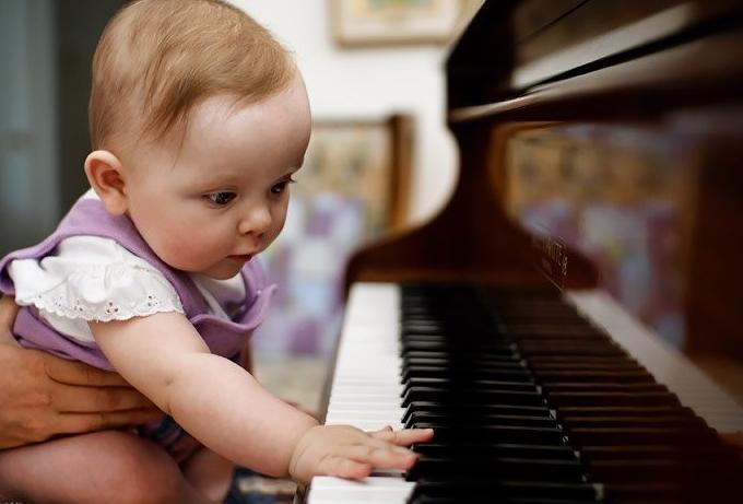 Грудной малыш нажимает пальчиками на клавиши фортепиано