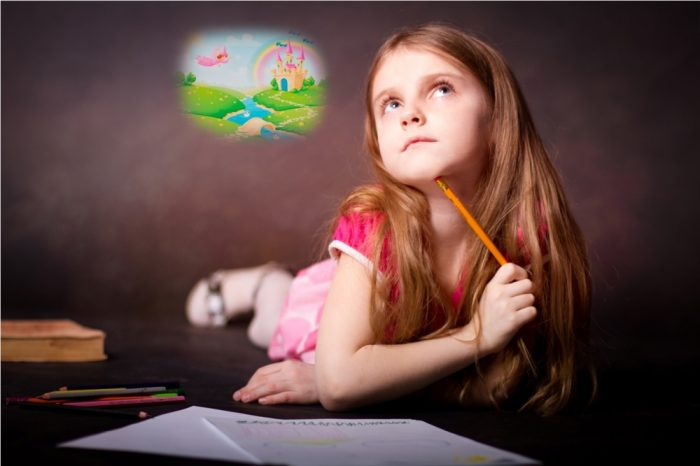 Девочка лежит на кровати с рисунком и карандашами и воображет сказочный мир