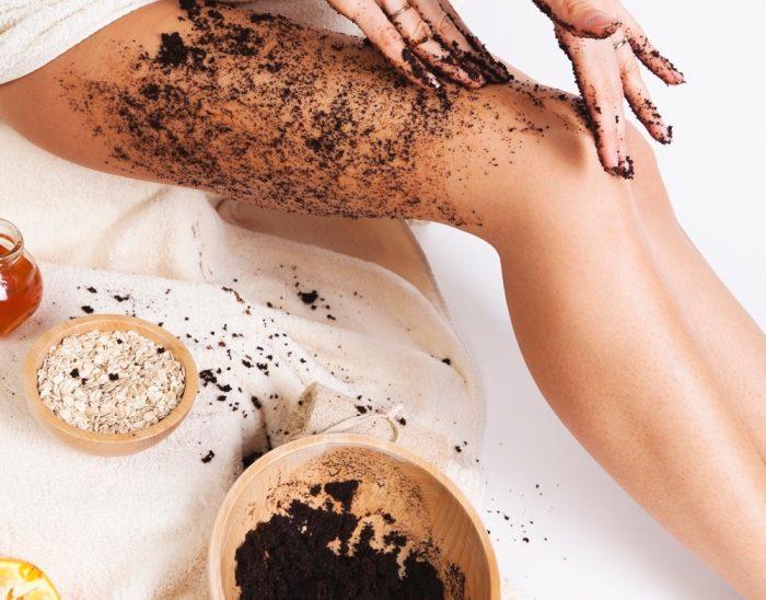 Девушка наносит на тело кофейный скраб