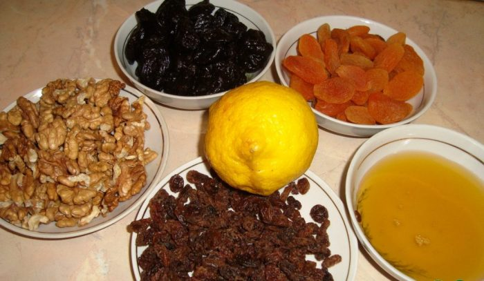 Изюм, курага, чернослив, грецкие орехи и мёд в тарелках на столе
