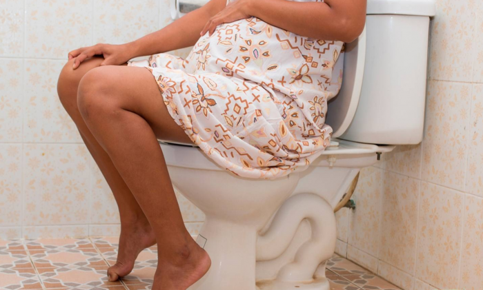Беременная женщина сидит на унитазе