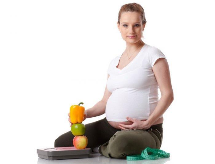 Беременная, весы и портновский метр