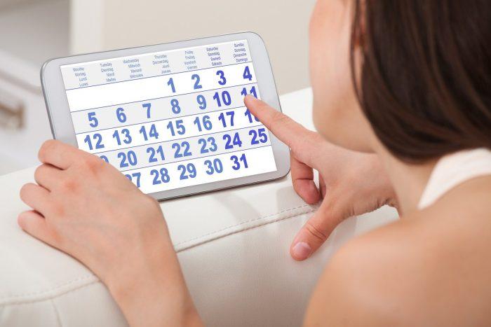 Женщина рассматривает календарь в планшете