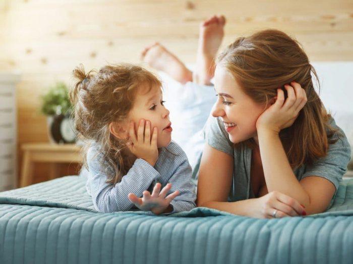 Мама и маленькая дочка лежат на кровати и мило беседуют