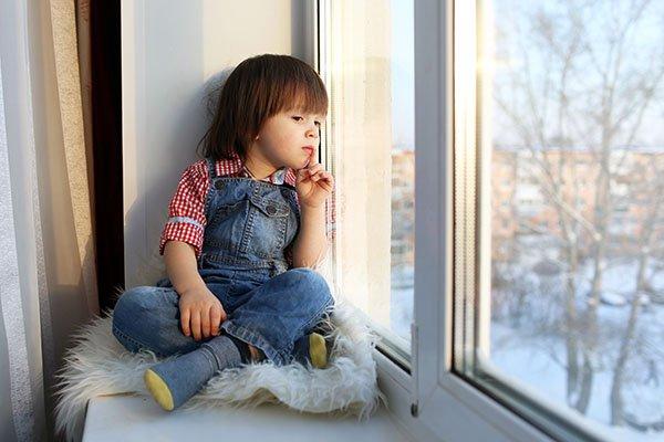 Ребёнок с интересом что-то разглядывает из окна