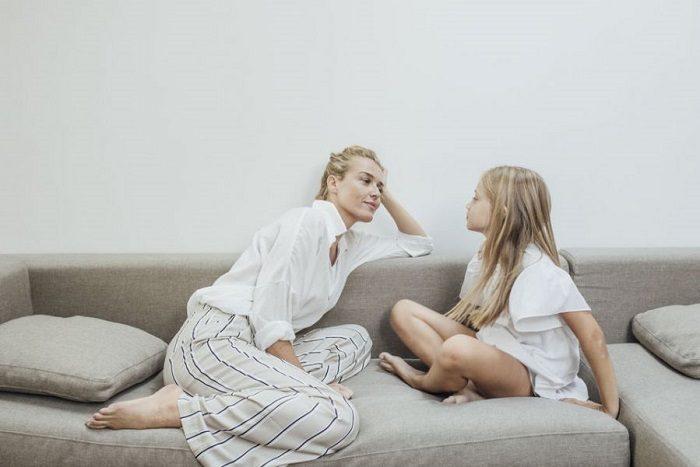 Мама беседует с дочкой, сидя на диване