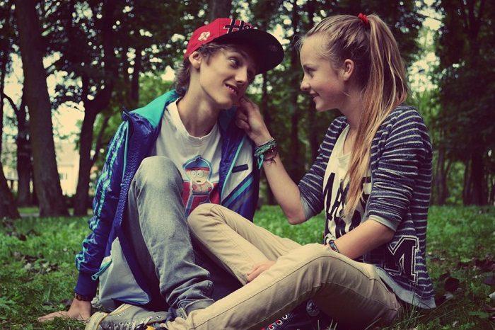 Мальчик и девочка подросткового возраста сидят на траве и нежно смотрят друг на друга