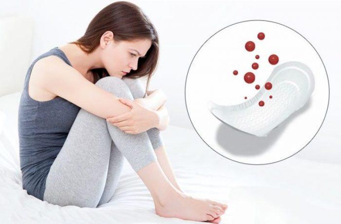 Женщина сидит на кровати, поджав ноги, рядом изображены капли крови над прокладкой