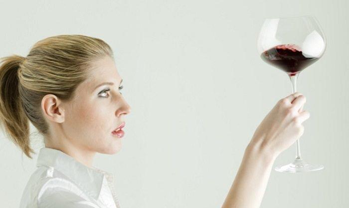 Женщина держит в руке бокал с небольшим количеством красного вина