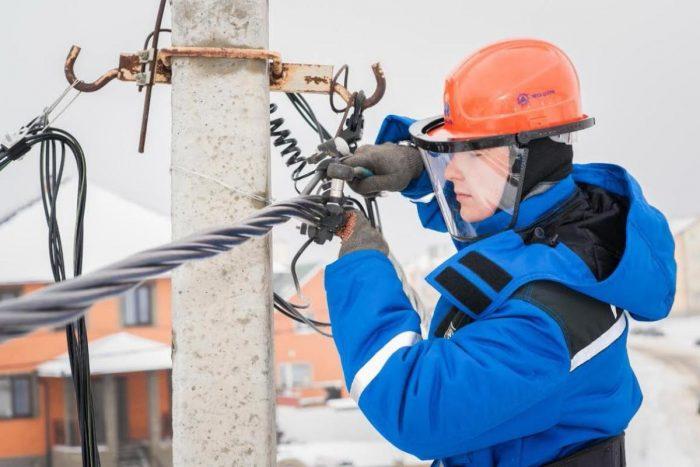 Электромонтёр крепит провода на столбе