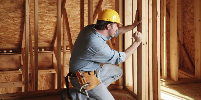 Плотник делает разметки при работе с деревом