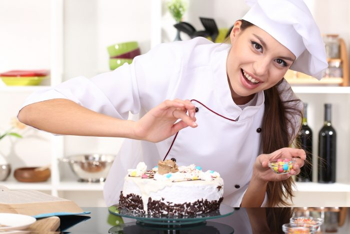 Девушка кондитер украшает торт