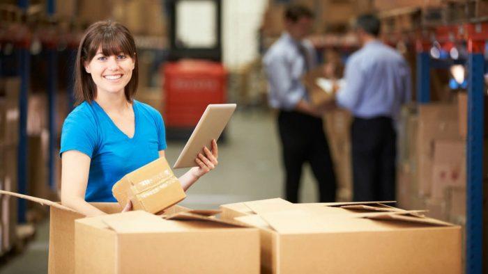 Девушка стоит возле коробок с планшетом в руке