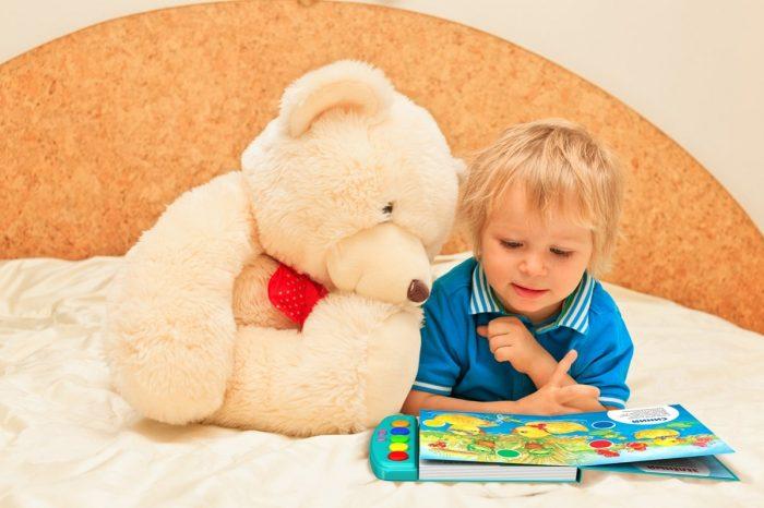 Малыш рядом с плюшевым мишкой смотрит книгу