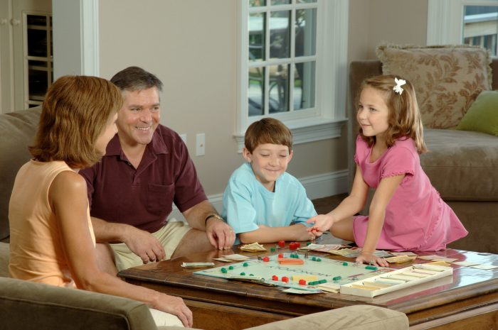 Члены семьи играют в настольную игру
