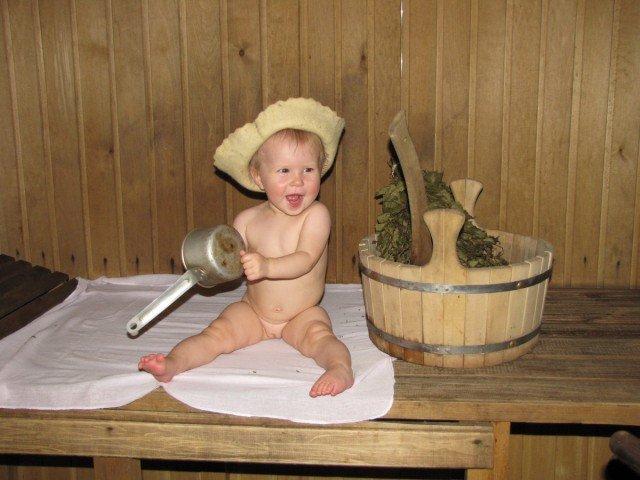 Маленькая девочка в парной сидит на полотенце и в шапочке