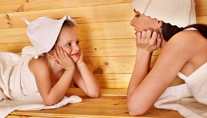 Девочка с мамой отдыхают в бане, закутанные в полотенце