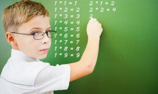 Мальчик пишет на доске примеры из таблицы умножения