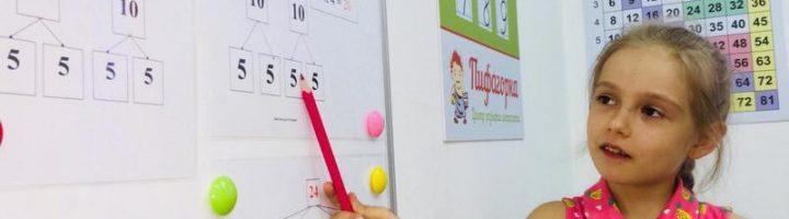 Девочка у доски карандашом показывает на выражение из таблицы