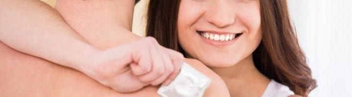Женщина обнимается с мужчиной и держит в руке презерватив