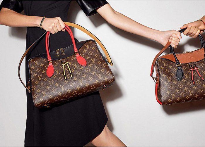 Женщина держит в руках сумки от Louis Vuitton