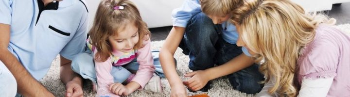Дети и родители играют на ковре