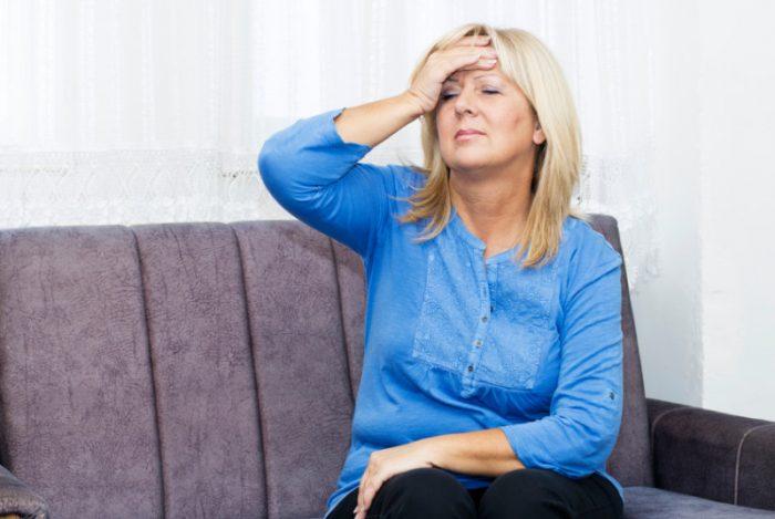 Женщина возрастом за сорок сидит на диване и, закрыв глаза, держится за голову