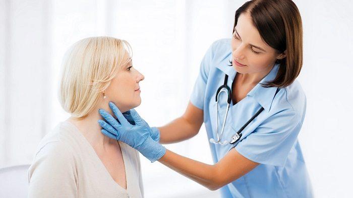 Врач прощупывает у пациентки область щитовидной железы