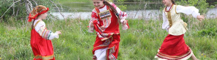 Дети в русских национальных костюмах играют в подвижную игру