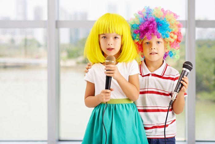 Девочка и мальчик держат микрофон