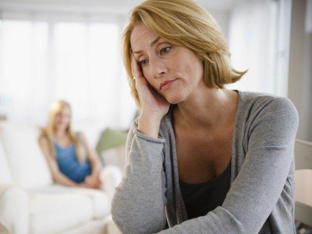 Женщина сидит, взявшись за голову, с тревожным видом, на заднем плане молодая девушка